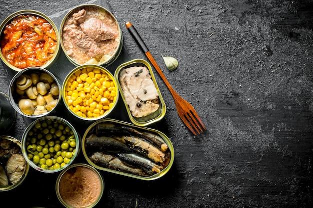 Ingeblikt voedsel in open blikjes. op zwarte rustieke achtergrond