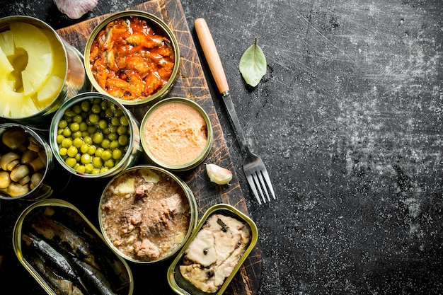 Ingeblikt voedsel in verschillende open blikjes op de snijplank. op donkere rustieke achtergrond