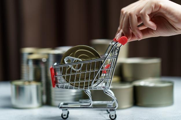 Ingeblikt voedsel in winkelwagen speelgoed met hand, groep van aluminium blikvoer.