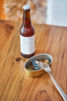 Ingeblikt voedsel met vis en een flesje bier een vork op een houten tafel