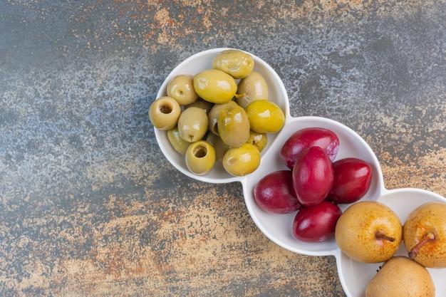 Ingeblikte appel, pruimen en olijven op een schotel
