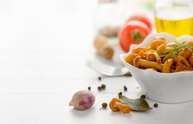 Ingeblikte champignons in een kom op een wit houten bord met olijfolie en kruiden kopieer ruimte