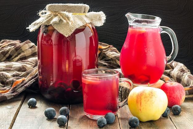 Ingeblikte fruitcompote van appels en sleedoorn in glazen kan en mok op houten tafel