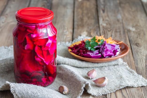 Ingeblikte gefermenteerde kool met bieten, wortelen en knoflook in een glazen kan.