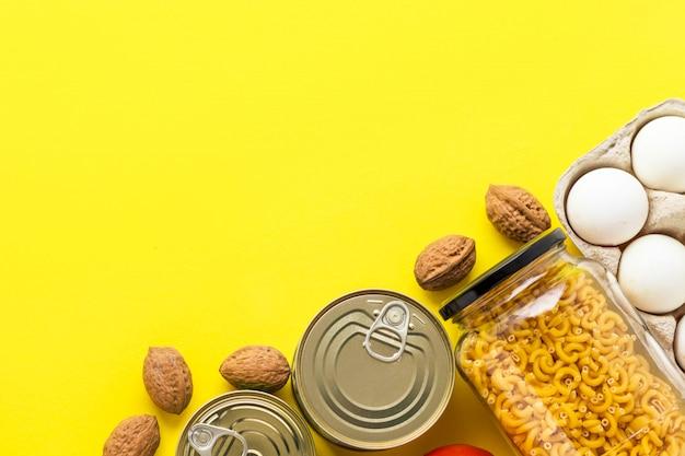 Ingeblikte goederen, walnoten, verse groenten, tomaat en komkommer, chichen eieren en pasta in glazen pot op roze achtergrond
