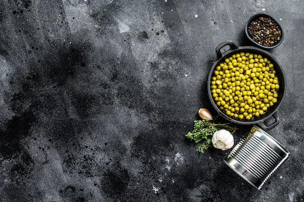 Ingeblikte groene erwten in een koekenpan. ingeblikt voedsel op zwart. bovenaanzicht. kopieer ruimte