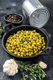 Ingeblikte groene erwten in een koekenpan. ingeblikt voedsel op zwart. bovenaanzicht