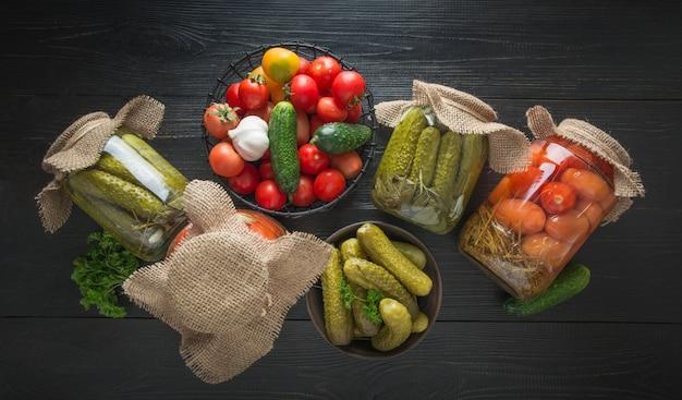 Ingeblikte groenten komkommer en tomaat in kom en glazen potten op donkere houten bord banner stilleven weergave van bovenaf.