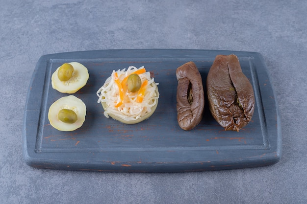 Ingeblikte groenten. zuurkool en gevulde aubergine op een houten bord.