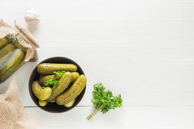 Ingeblikte komkommer in glazen potten en in een kom