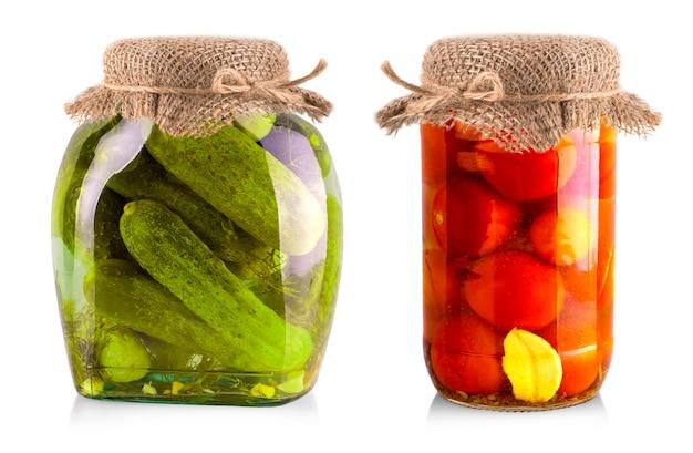 Ingeblikte komkommers en tomaten in glazen potten op wit wordt geïsoleerd