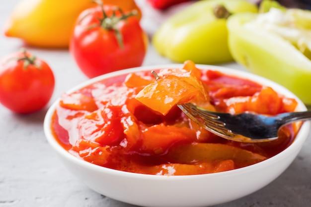 Ingeblikte lecho van de paprika's en tomaten, oogsten voor de winter