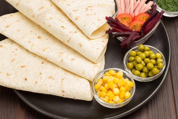 Ingeblikte maïs en groene erwten in glazen kommen met tortillawraps