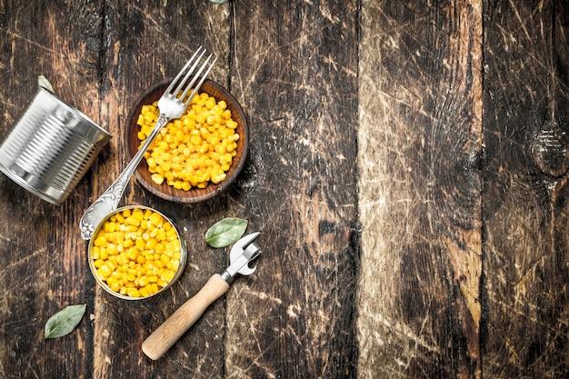Ingeblikte maïs in een blikje met opener op houten tafel.