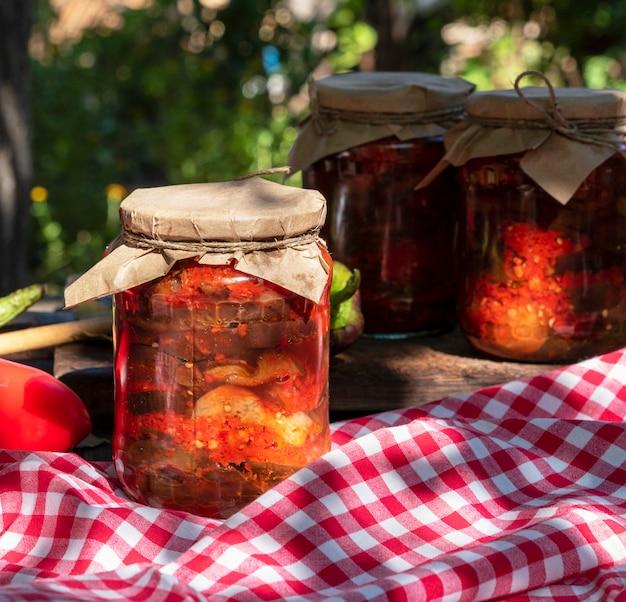 Ingeblikte plakken aubergine in pittige groentesaus in glazen potten