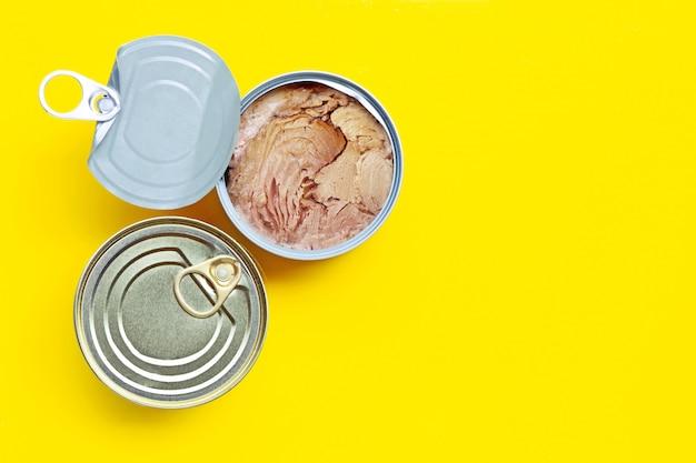 Ingeblikte tonijn op gele achtergrond. kopieer ruimte