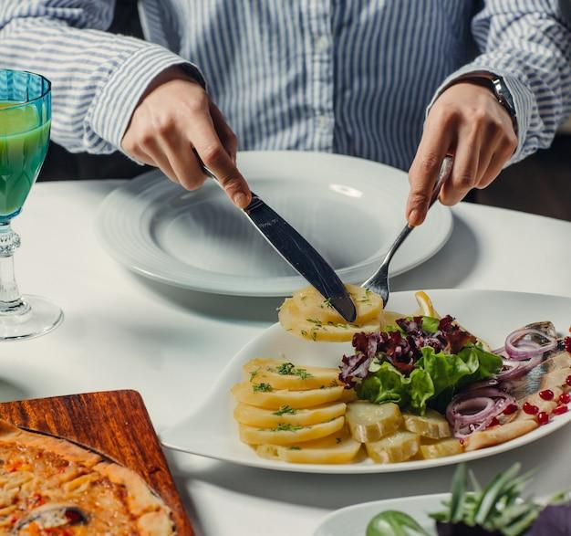 Ingeblikte vis met gekookte aardappelschijfjes, komkommer augurken, rode ui, sla, granaatappel