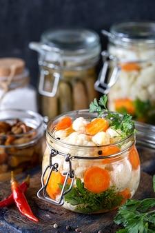 Ingelegde bloemkool met wortelen in een glazen pot op een donkere houten tafel. gefermenteerd voedsel.