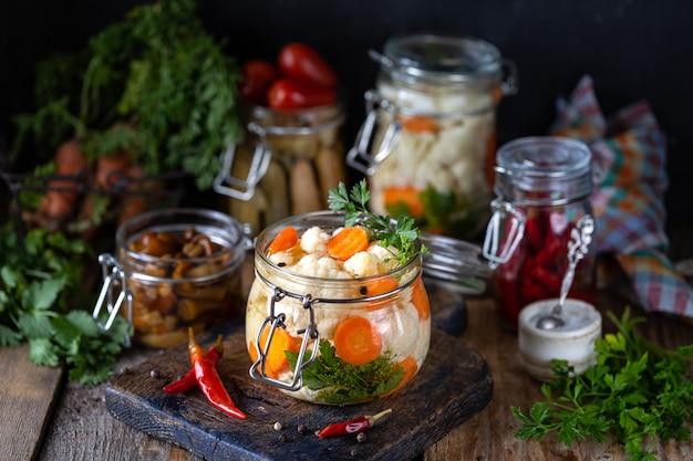 Ingelegde bloemkool met wortelen in een glazen pot op een donkere houten tafel.