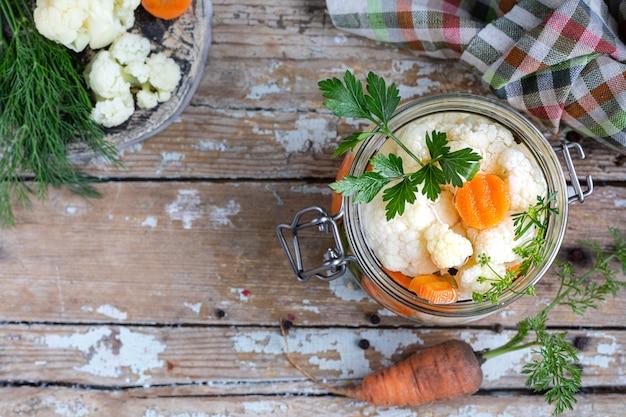 Ingelegde bloemkool met wortelen in een glazen pot op een oude houten tafel ... bovenaanzicht