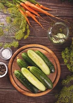 Ingelegde gemarineerde komkommers op een keukentafel met dille, kruiden en knoflook