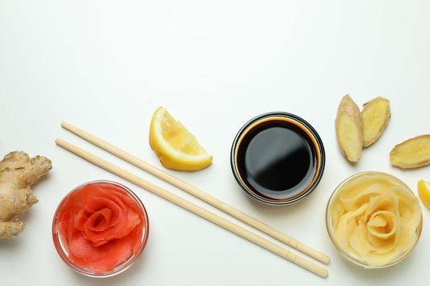Ingelegde gember, sojasaus, gember, eetstokjes en citroen op witte ondergrond