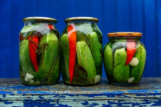 Ingelegde ingelegde komkommers in glazen potten op een houten bankje in het gat van een huis in het dorp. blauwe achtergrond. vooraanzicht. traditionele voorbereidingen voor de winter.