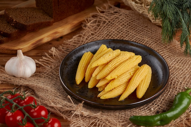 Ingelegde kleine maïs op houten