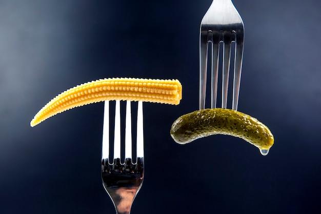 Ingelegde komkommer en maïs op een vorkclose-up op donkerblauw. voedsel en groenten
