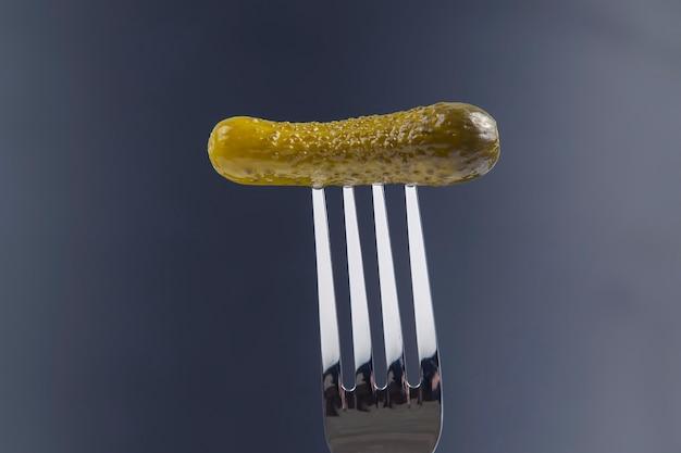 Ingelegde komkommer op een vork. voedsel en groenten