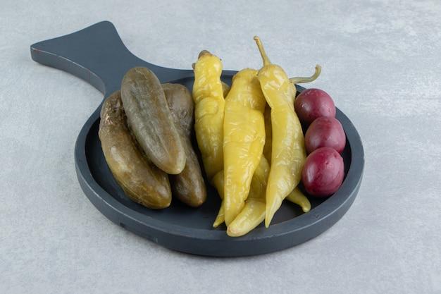 Ingelegde komkommers en chilipepers op donker bord.