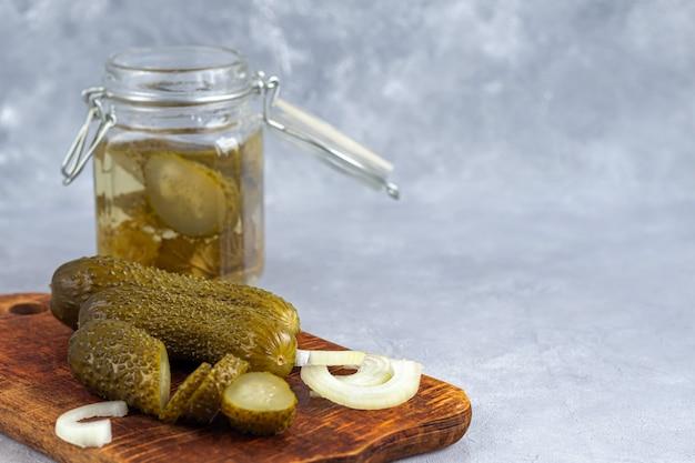 Ingelegde komkommers in een glazen pot en op een houten bord. gefermenteerd voedsel op een grijze achtergrond. kopieer ruimte.