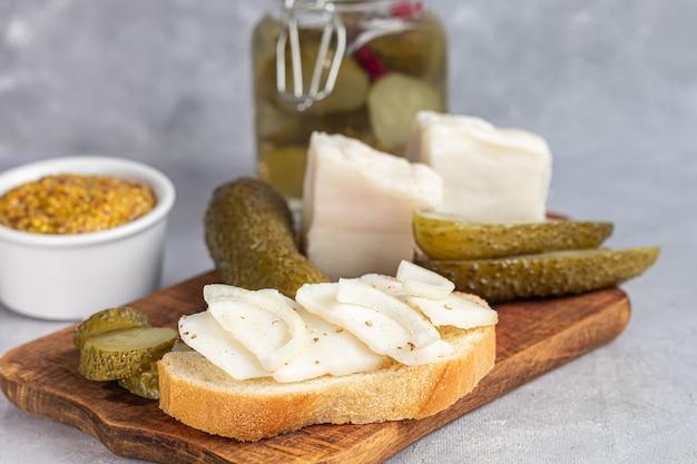 Ingelegde komkommers in een glazen pot op een houten bord en een sandwich met spek. mosterdbonen op de achtergrond. gefermenteerd voedsel. kopieer ruimte.