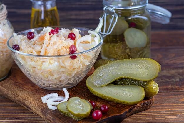 Ingelegde komkommers in een glazen pot op een houten bord en zuurkool met veenbessen. gefermenteerd voedsel. kopieer ruimte.
