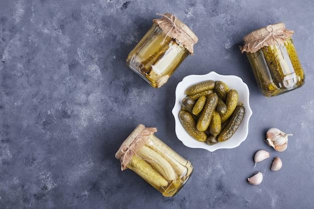 Ingelegde komkommers in kom en glazen potten op blauwe achtergrond met knoflook.