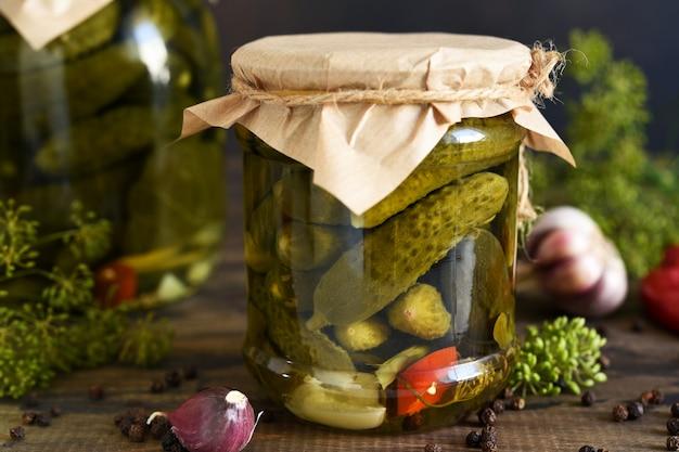 Ingelegde komkommers met dille en knoflook in een glazen pot.