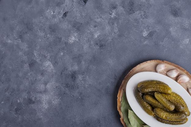 Ingelegde komkommers op witte plaat met knoflook en bladeren op blauwe achtergrond.