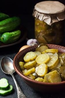 Ingelegde komkommersalade in een kom en pot op zwarte achtergrond