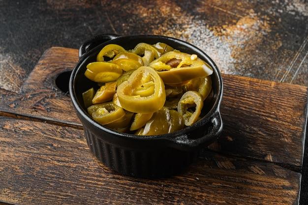 Ingelegde of ingeblikte jalapeno-paprika's, op oude donkere rustieke achtergrond