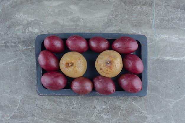 Ingelegde olijven en appels op houten plaat