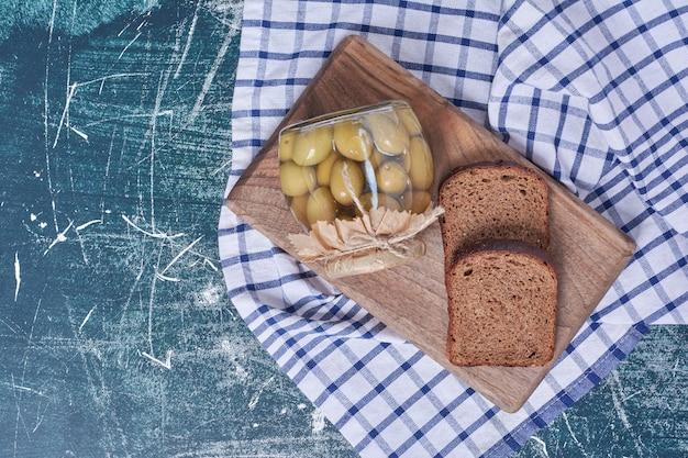 Ingelegde olijven in glazen pot met zwarte sneetjes brood op blauw.