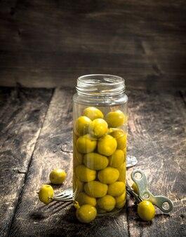 Ingelegde olijven in glazen pot op houten tafel