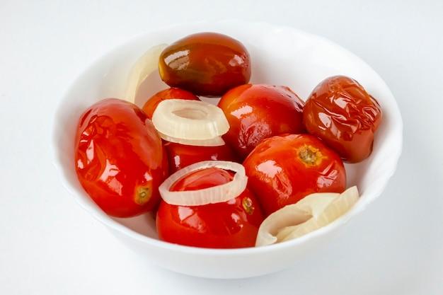 Ingelegde rode tomaten op een witte plaat.