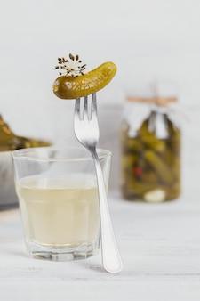 Ingelegde sap, augurk en gemarineerde komkommer in een kom. schoon eten, vegetarisch voedselconcept