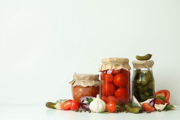 Ingelegde tomaten, komkommers, adjuca en ingrediënten op wit