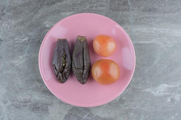 Ingemaakte aubergine en tomaat op roze plaat.