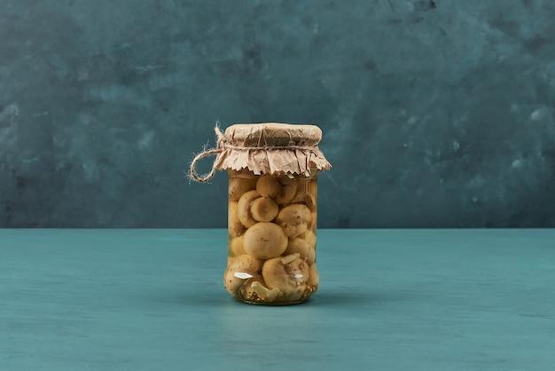 Ingemaakte champignons in een glazen pot op blauwe tafel.