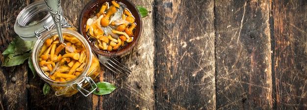 Ingemaakte champignons in een kom met kruiden en specerijen op een houten tafel.