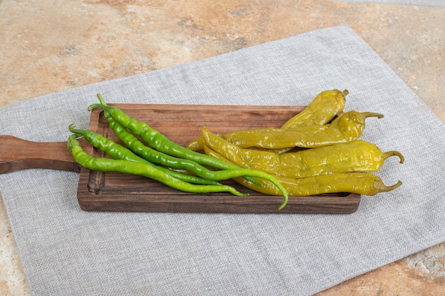 Ingemaakte en verse groene paprika's op houten snijplank
