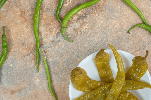 Ingemaakte en verse groene paprika's op witte plaat